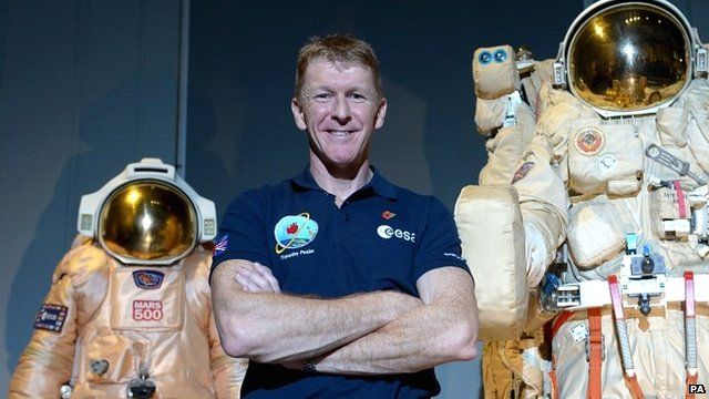 Tim Peake poses beside spacesuits as he talks to reporters at the Science Museum, London