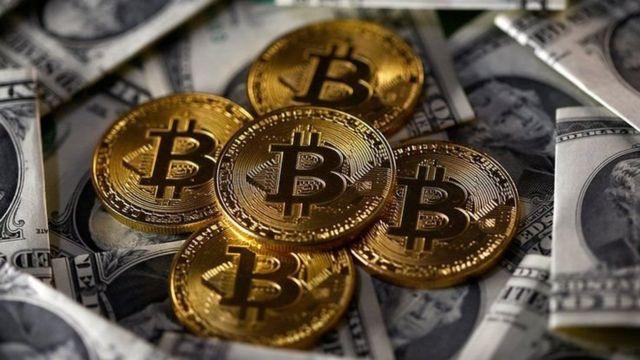 Billetes de dólares y monedas que representan bitcoins