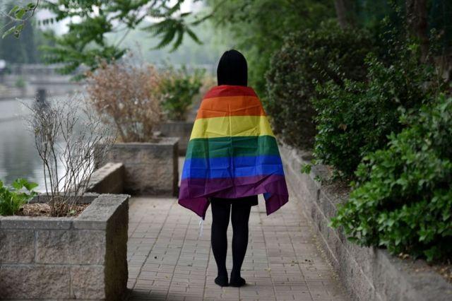 一名北京的學生身披象徵性少數群體的彩虹旗。