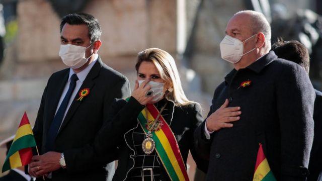La expresidenta interina de Bolivia, Jeanine Añez, con una mascarilla junto al ministro de Gobierno Arturo Murillo (derecha) y el ministro de la Presidencia, Yerko Núñez (izquierda), durante las celebraciones del Día de la Independencia en medio de la pandemia de coronavirus el 6 de agosto de 2020 en La Paz. Bolivia.