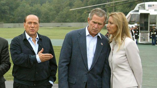 Джордж Буш слушает переводчика в то время, как Сильвио Берлускони общается с прессой по своему прибытии в Кэмп-Дэвид, 14 сентября 2002 года
