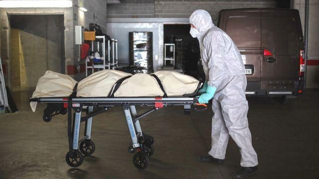 В испанской Жироне сотрудники похоронной службы в защитных костюмах перевозят тело жертвы коронавируса