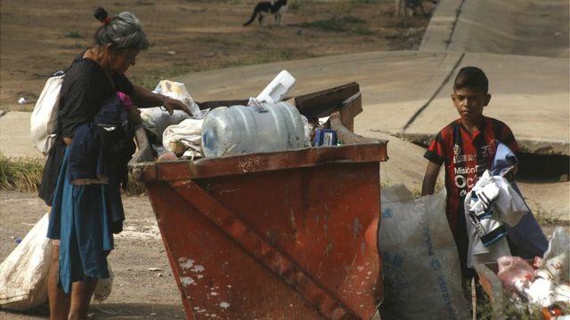 Madre en Venezuela busca en la basura con su hijo