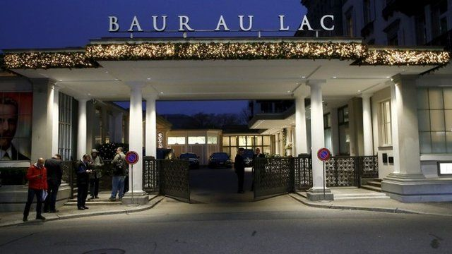 Members of the media stand outside the Baur au Lac hotel