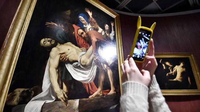 """Una mujer tomándole foto a """"El descendimiento"""", de Caravaggio."""