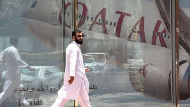 رجل يمشي أمام طائرة تابعة لخطوط الطيران القطرية