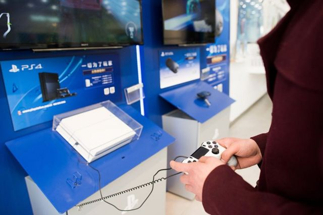 A person playing a Sony PlayStation 4