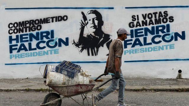 Um trabalhadro passa em frente a uma propaganda eleitoral de Henri Falcón pintada em um muro