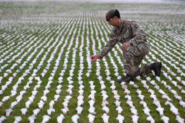 士兵將一個布裹玩偶放入裝置藝術品中。