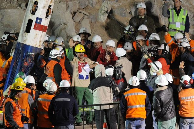 Chilean miner Juan Illanes celebrates after coming out of the Phoenix capsule, which brought him to the surface on 13 October 2010