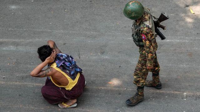 Um soldado ao lado de um homem detido durante uma manifestação contra o golpe militar em Mandalay em 3 de março de 2021