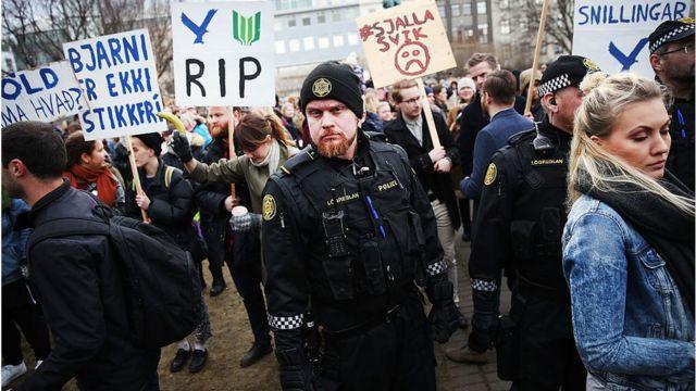 Protestas en Islandia. Policía mira hacia la cámara mientras es rodeado de manifestantes y carteles en oposición al gobierno.