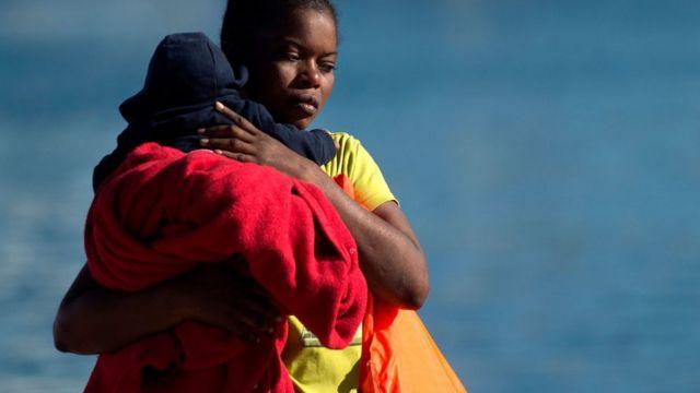 Mujer cargando a un niño migrante.