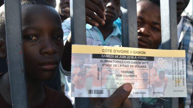 Umufana w'ikipe ya Cote d'Ivoire afise itike yo kuraaba umupira kuri stade de Paix, hagati ya Cote d'Ivoire na Gabon