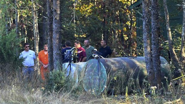 Todd Kohlhepp está en la zona boscosa junto a unos contenedores de forma cilíndrica