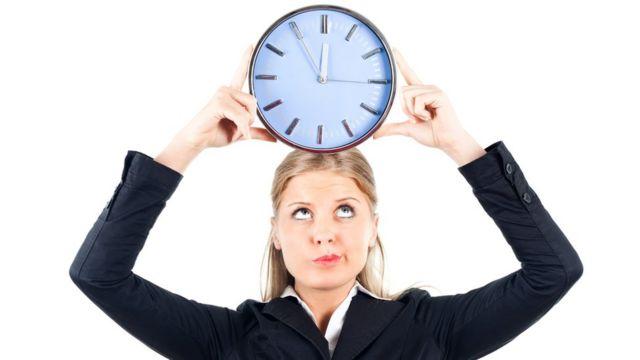 Mulher com relógio na cabeça