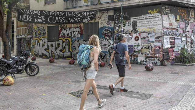 """Une banderole déployée dans le centre d'Exarchia indique aux touristes qu'ils sont des """"cibles"""" et qu'ils doivent """"rentrer chez eux""""."""