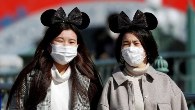 Visitors wearing protective face masks and Mickey Mouse costumes, following an outbreak of the coronavirus,