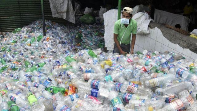 plastik şişe toplayan bir Hintli.