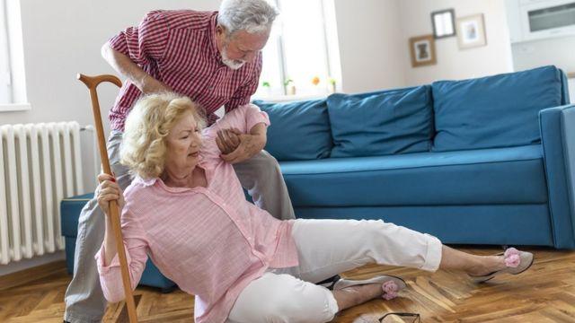 Hombre ayudando a una mujer que se cayó al suelo