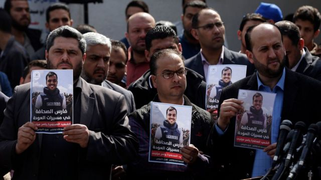 صحفيون فلسطينيون يحملون صور المرتجى