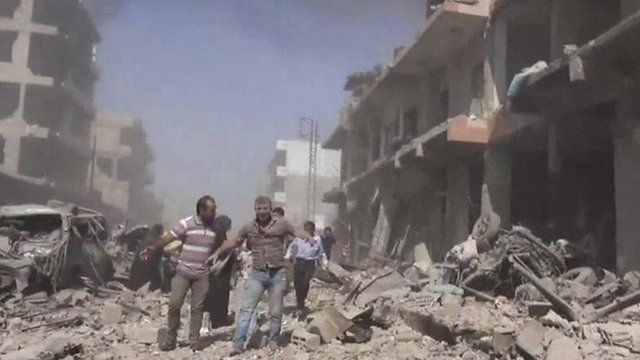 People walk in the rubble in Qamishli