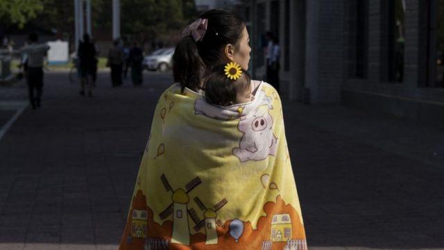பியாங்யாங்கில் தன் குழந்தையுடன் நடந்து செல்லும் பெண்
