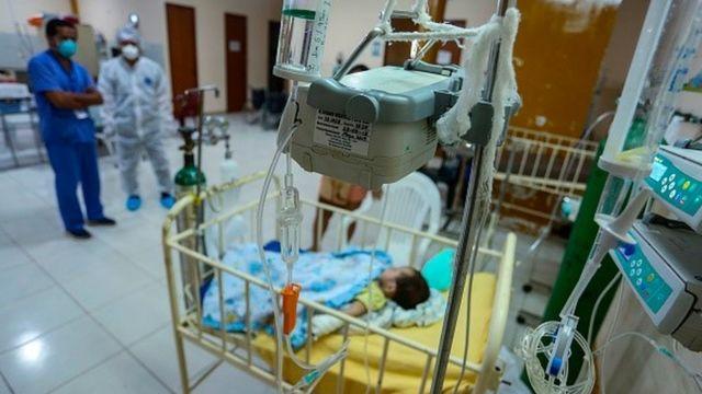Profissionais da saúde olham para bebê internado em leito pediátrico