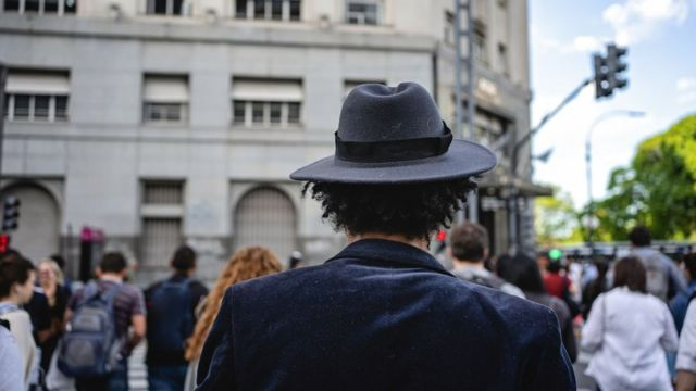 A man wearing a hat with his back to camera crosses a road