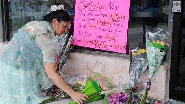 Una mujer deposita flores en homenaje a Christina Grimmie