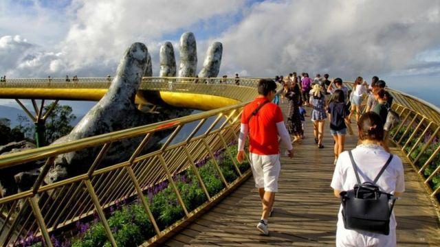 """Turis berjalan di Cau Vang """"Jembatan Emas"""" di Ba Na dekat Danang."""