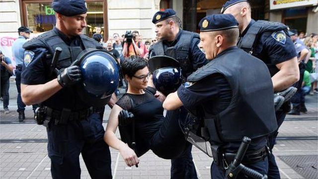 Policija nosi učesnicu Hoda za slobodu u rukama