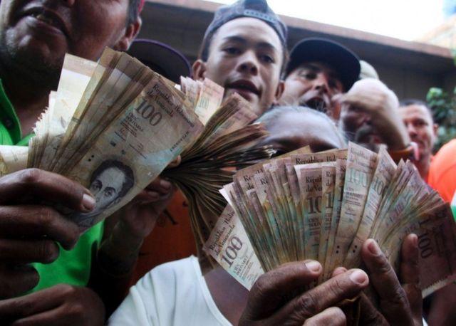 वेनेजुएला सेंट्रल बैंक के बार प्रदर्शन करते लोग.