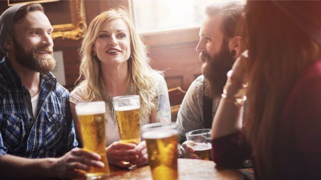 Four friends sitting at a pub table drinking a pint of beer.