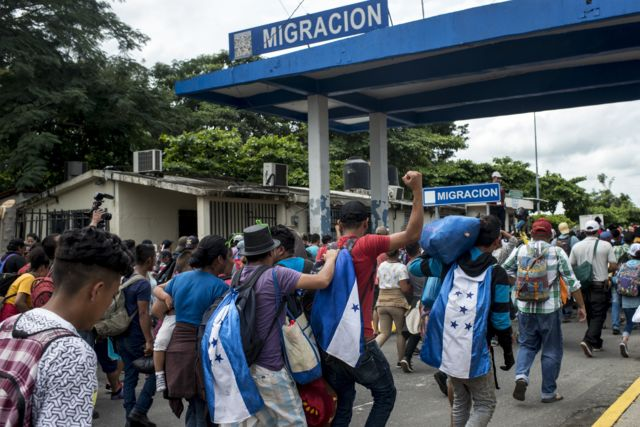 Thousands of Honduran migrants cross the border bridge between Guatemala and Mexico, while hundreds of federal police and soldiers wait on the other side.