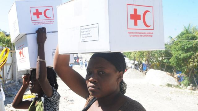Mujeres cargan sobre sus hombros cajas que contienen kits anti cólera.