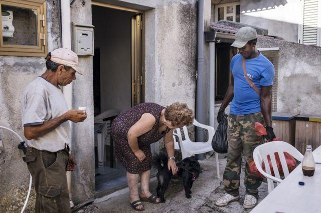 Biagio et Daniel discutent avec une habitante de la ville lors d'une opération de porte-à-porte visant à recycler
