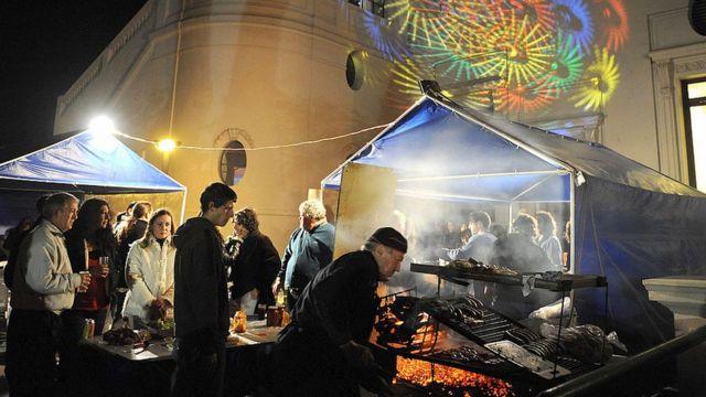 Gente haciendo fila para comer carne en la Noche de la Nostalgia en Maroñas.
