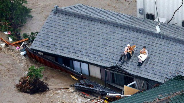 Residents holding dogs wait for help, sitting on the roof of their house in the flooded city of Joso