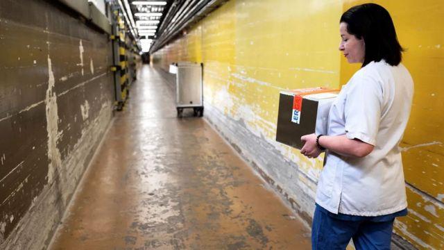 Una investigadora en un pasillo con paredes descascaradas del Instituto Eliava.