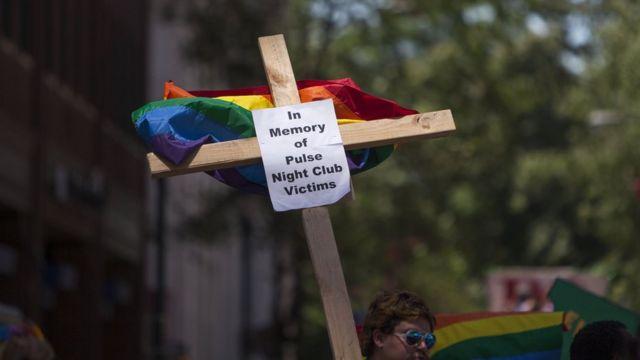 """Una cruz con la bandera gay y la inscripción: """"En memoria de las víctimas del club nocturno Pulse""""."""