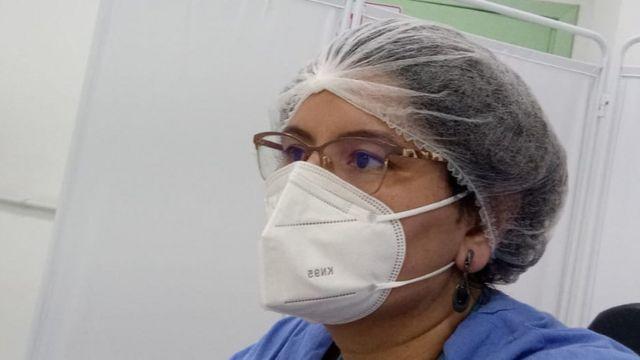 Priscila aparece de máscara, touca e de perfil, sentada em consultório