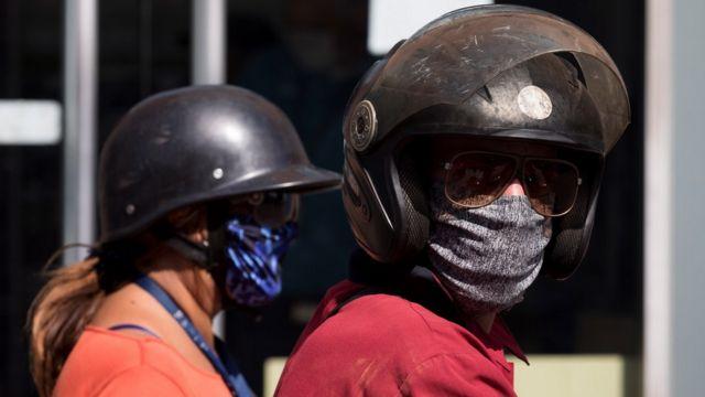 Una pareja con mascarillas de tela y cascos en Caracas, Venezuela