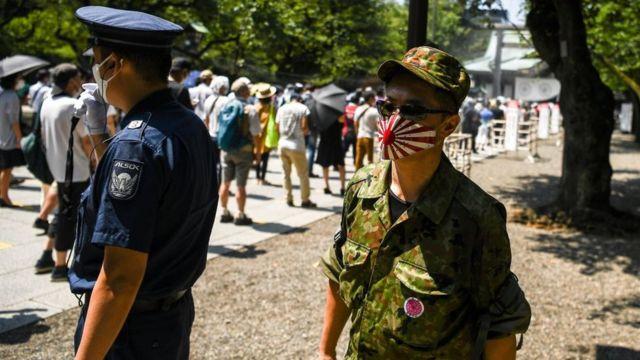 Un hombre con una máscara protectora con la bandera del Sol Naciente en Tokio agosto de 2020.