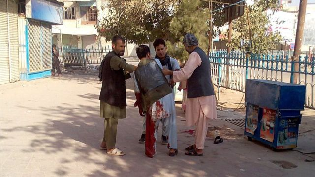 Afghan men assist a wounded civilian in a street of Kunduz