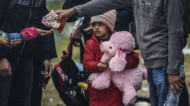 Una pequeña refugiada con un perro de peluche.