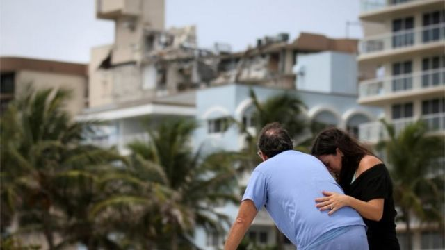 Two people in front of the collapsed tower