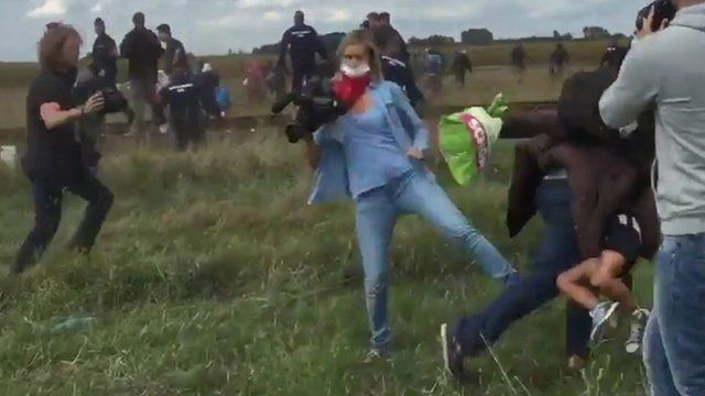 A Hungarian camerawoman appears to kick a migrant