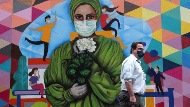 Hombre delante de un mural con un dibujo de mujer con máscara.