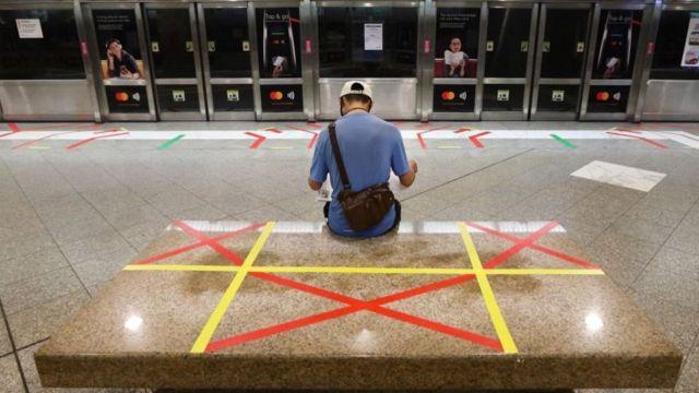 Homem sentado em um banco com marcações de distância social